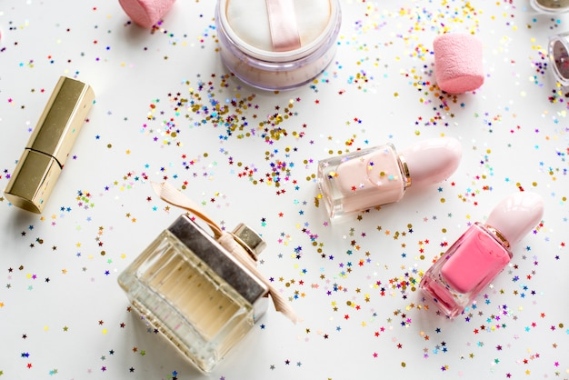 Cosmetic objects and confetti isolated on background