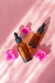 ピンクの表面に化粧油と花。美容処置。健康な肌。