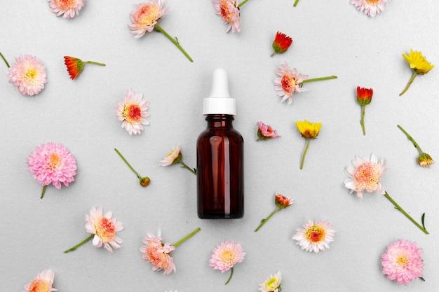 Бутылка косметического масла на плоской планировке цветочных бутонов