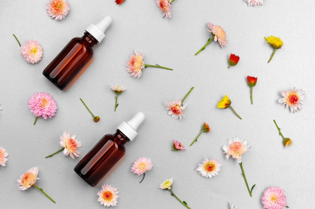 Бутылка косметического масла на плоской стене с цветочными бутонами