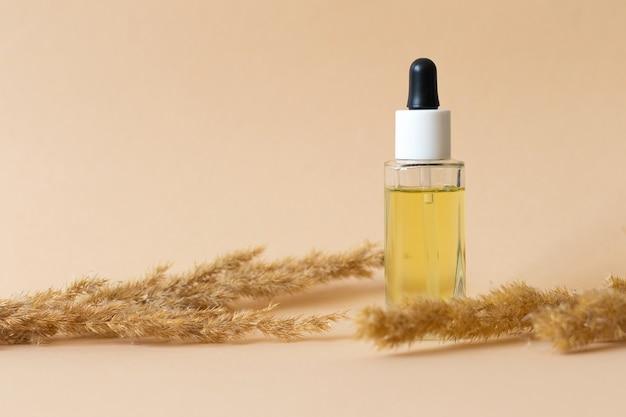 Косметическое масло для лица и тела, бутылка с маслом на бежевом фоне, место для текста. фото высокого качества