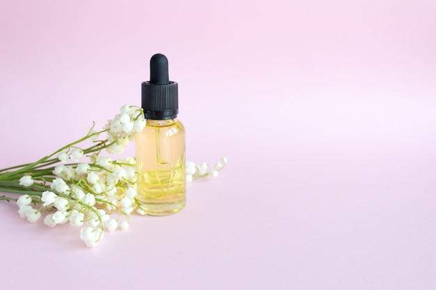핑크에 물방울의 병에 화장품 오일. 은방울꽃 에센셜 오일