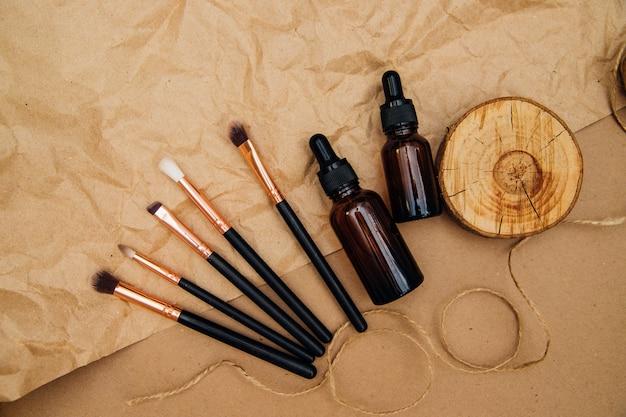 ピペットと化粧ブラシが入った容器に入った化粧油は、ベージュのしわくちゃのクラフト紙の上にあります。アロマテラピー用エッセンシャルオイル。モノクロ画像。