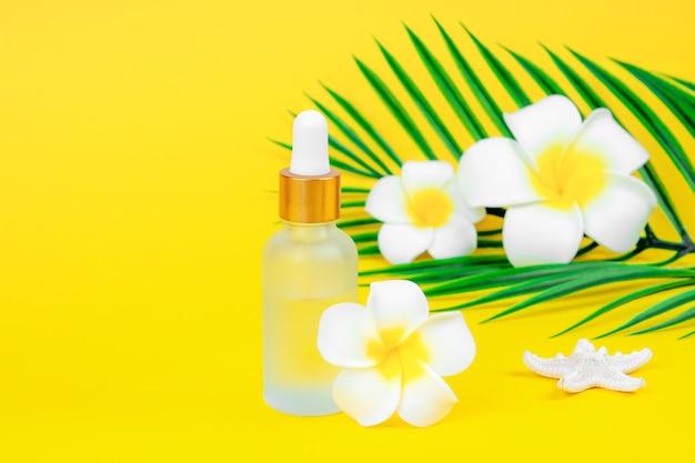 Косметическое масло в бутылке-капельнице с цветами плюмерии на желтом фоне с местом для текста.