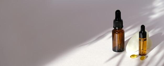 トレンディな影と白い背景の上のガラス瓶の化粧品オイル。ゼロウェイストコンセプト