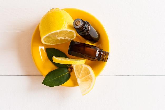Косметическое масло или эфирное масло лимона в двух флаконах с дозатором на желтой тарелке с дольками лимона. белый деревянный фон.