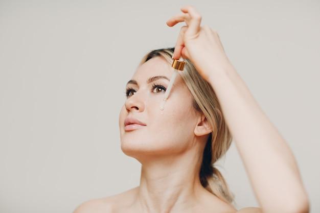 젊은 성인 여자의 얼굴에 피펫으로 적용하는 화장품 오일 로얄 젤리