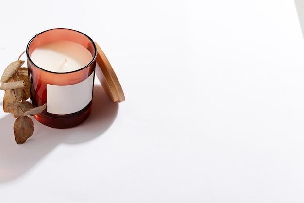화장품 또는 어두운 호박색 유리 병, 고립 된 흰색 배경에서 촛불. 포장 모의