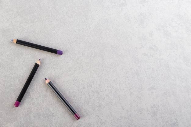 Cosmetic pencils of make up placed on a stone table .