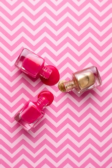 Cosmetic pink and gold nail polishes on pink