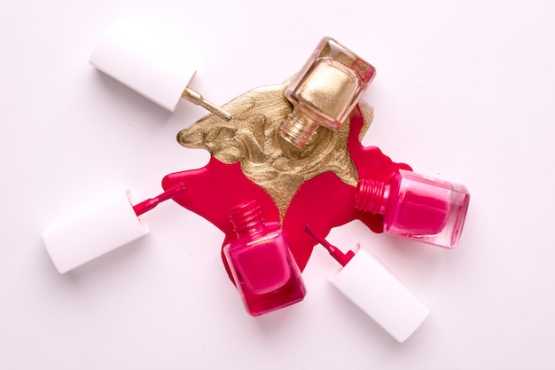Cosmetic pink and gold nail polishes on white