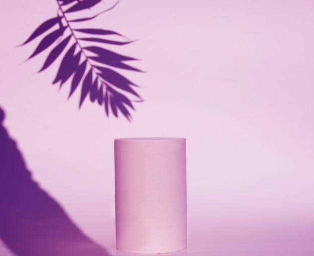 ピンクの化粧品のピンクの表彰台と葉の影