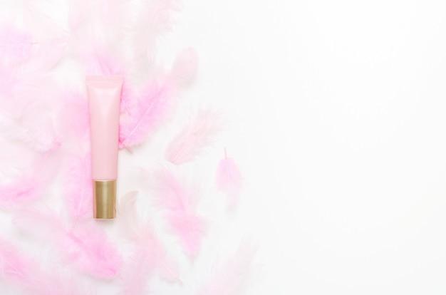 화장품 핑크 튜브와 깃털 평면도 구성. 스킨 케어 화장품 제품, 보습 크림 개념.