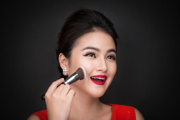 化粧品パウダーブラシ。完璧なメイクと赤い唇で頬にほお紅を塗るアジアの女性