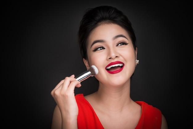 코스메틱 파우더 브러쉬. 완벽한 화장과 붉은 입술로 뺨에 블러셔를 바르는 아시아 여성