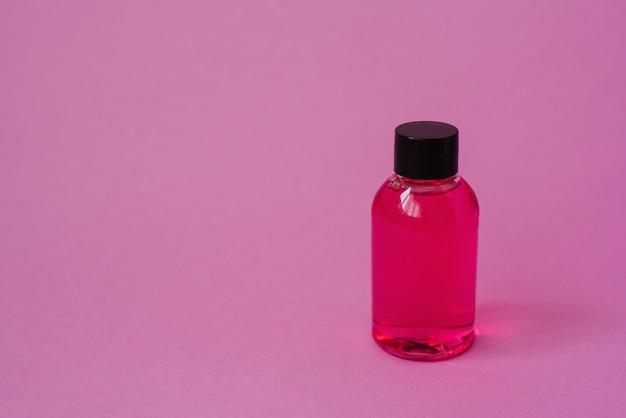 바디 스킨 케어 화장품 또는 분홍색 배경에 머리카락 화장품 제품 병. 복사 공간, 배너 또는 템플릿 측면보기. 미용 제품의 개념. 브랜딩 레이아웃을위한 빈 레이블.