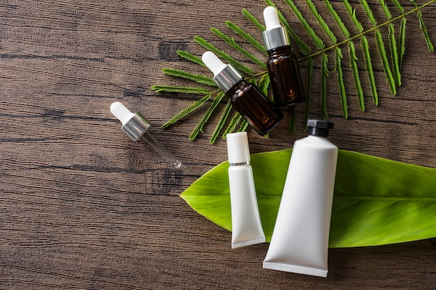 Cosmetic product and essential oil bottle on leaves over wooden table