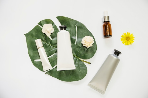 Cosmetic product and flower on monstera leaf and essential oil bottle on white background