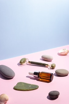 ピペットとグアシャエスクレーパーとローラーを備えたガラス瓶に入った化粧品。近くの滑らかな石。スキンケア、美容の概念。