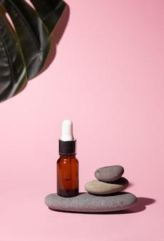 분홍색 배경에 피펫이 있는 유리병의 화장품. 근처에 부드러운 돌. 피부 관리, 화장품의 개념입니다.