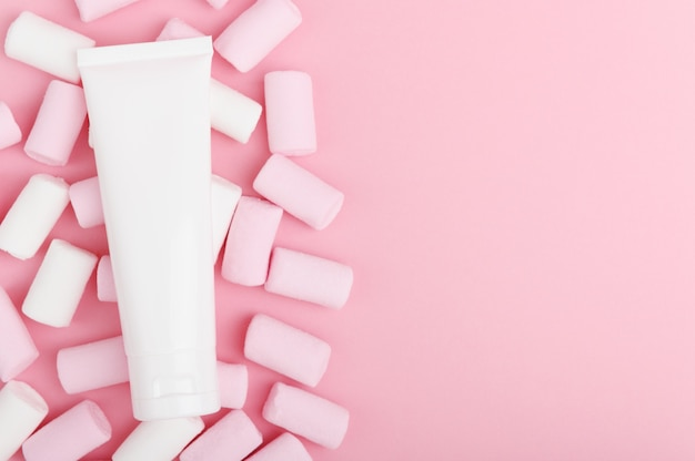 Косметический продукт в белой упаковке на пастельном фоне с красочными конфетами.