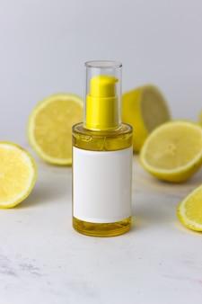 Косметический продукт желтого цвета на фоне лимонов на белом фоне