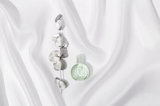 흰색 실크 천에 은색으로 칠해진 유칼립투스 가지가있는 화장품, 투명 젤 또는 크림