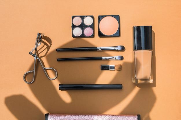 Косметические продукты и кисти на оранжевом фоне