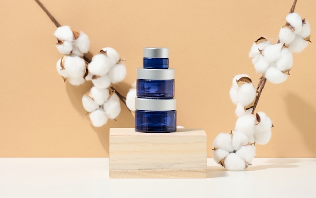 Cosmetic products in a blue glass jar with a gray lid stand on a wooden podium made of cubes. blank for branding products, moisturizer on beige background