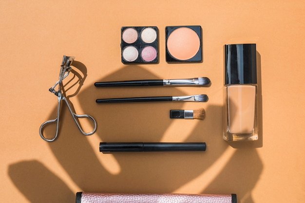Cosmetic products and brushes on orange background