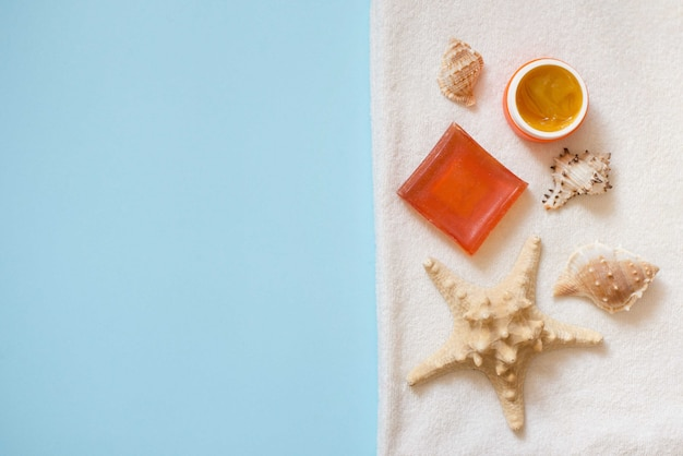 Cosmetic products cream and orange soap with shells and sea star on white towel