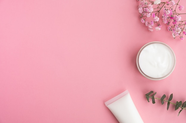 Cosmetic products, flowers and eucalyptus leaves on pink.