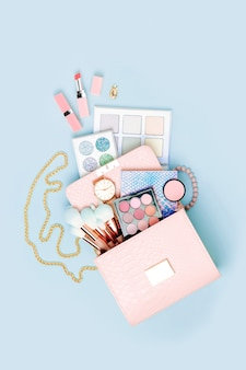 パステルブルーの背景に化粧バッグから流れる化粧品フラットレイトップビュー