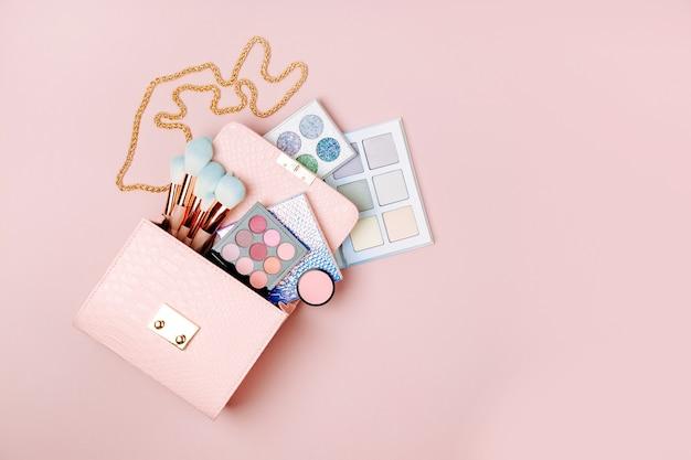 パステルピンクの背景に化粧バッグから流れる化粧品フラットレイトップビュー