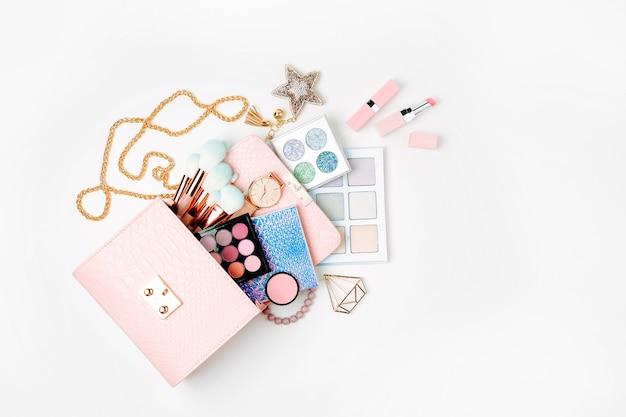白い背景の上の化粧バッグから流れる化粧品