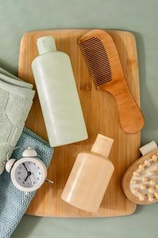 緑の背景の髪とスキンケアのための化粧品。テキスト用のスペース。フラットレイ構成