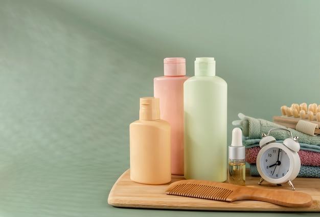 緑の背景の髪とスキンケアのための化粧品。テキスト用のスペース