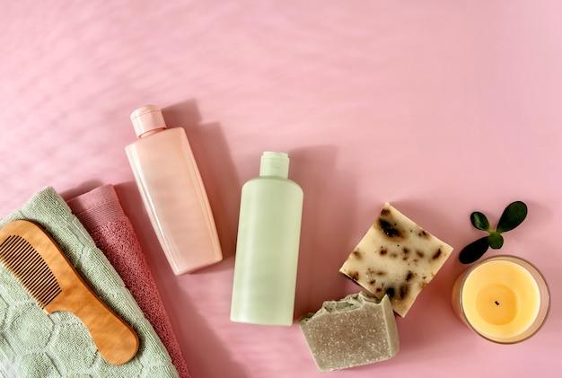 ピンクのバックグラウンダーのヘアケアやスキンケア用の化粧品。テキスト用のスペース。フラットレイ構成