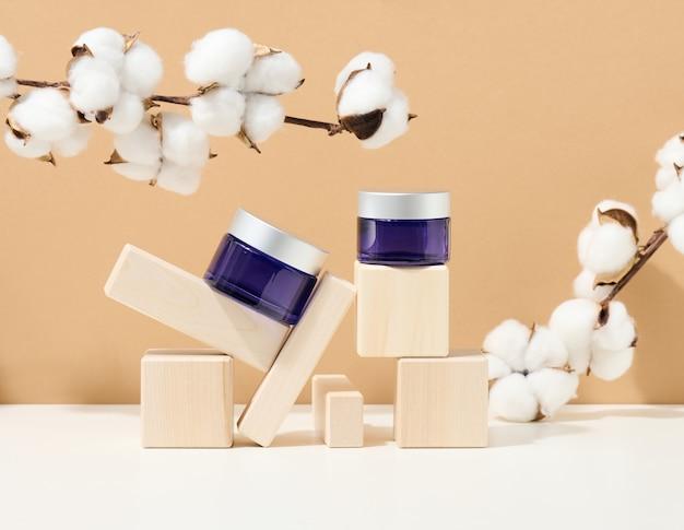 Косметическая продукция в синей стеклянной банке с серой крышкой стоит на деревянном подиуме из кубиков. заготовка для брендинга продуктов, увлажняющий крем на бежевом фоне