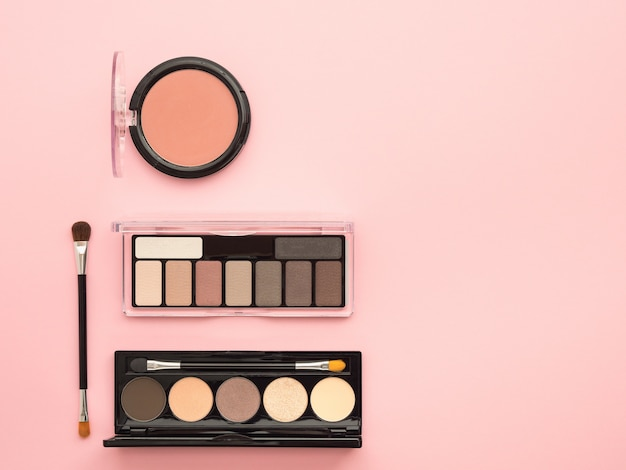 Cosmetic products on pink background.