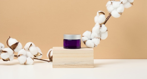 Cosmetic products in a purple glass jar with a gray lid stand on a wooden podium made of cubes. blank for branding products, moisturizer on beige background