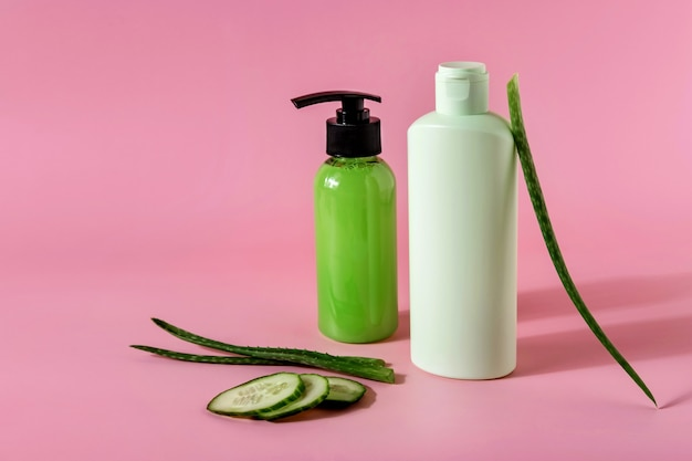 Cosmetic products with aloe vera and cucumber  on pink backgroundr. space for text.