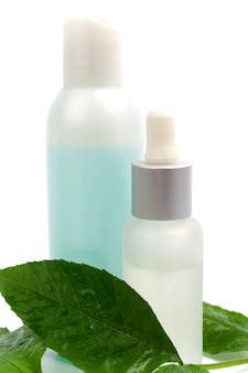 Cosmetic products with green leaf on white background