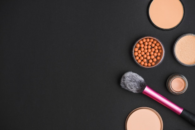 Cosmetic products with makeup brush on black backdrop