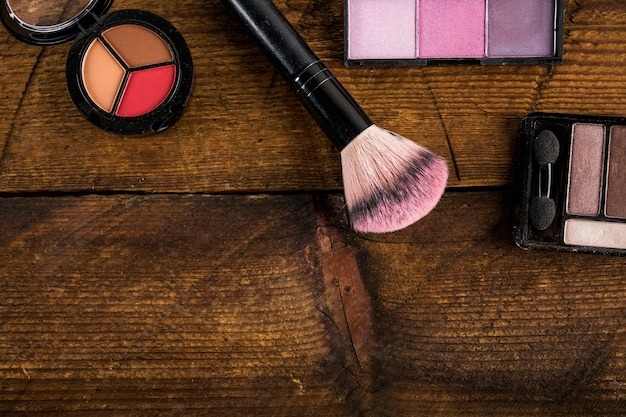 Cosmetic products with makeup brush on wooden background