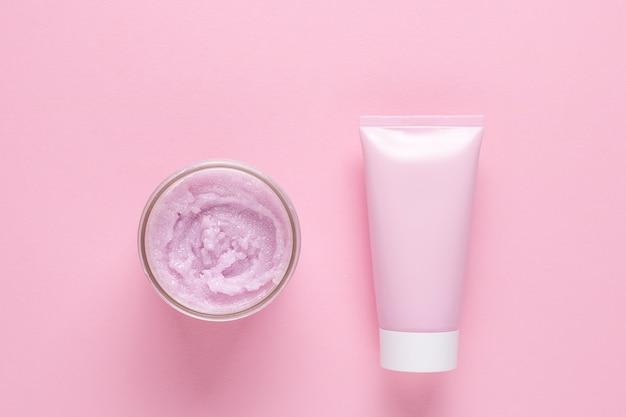 얼굴과 몸을 위한 화장품 스크럽과 분홍색 배경에 크림이나 마스크를 위한 화장품 튜브