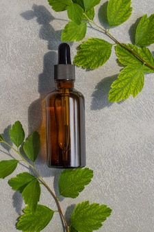Cosmetic serum, oil or plant extract in a dark bottle with a dropper on a background of plant leaves.
