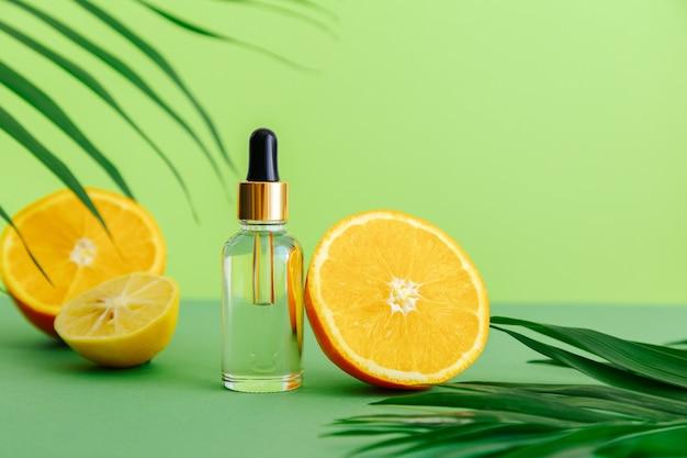 피펫 스포이드가 있는 유리병에 화장품 혈청 비타민 C. 감귤류 성분이 있는 오렌지 에센셜 오일 비타민 C와 야자수 잎은 녹색 배경에 있습니다. 천연 스킨 케어 페이스 코스메틱. 프리미엄 사진