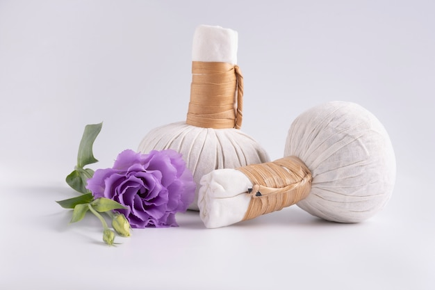 Cosmetic set for massage with bags of herbs and purple flower on white surface