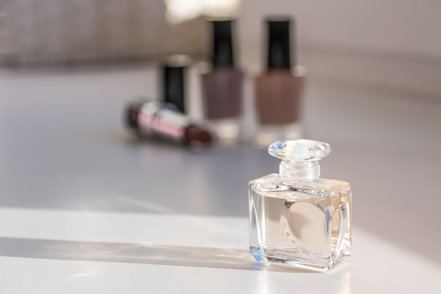Cosmetic set. nail polish, lipsticks and perfume. selective focus on front bottle.